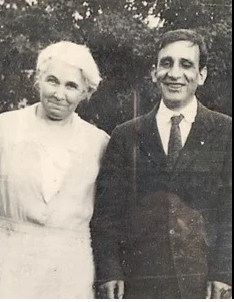 A black and white photo of Francis and Laura Ierardi standing together with trees in the background.  Laura is wearing a light colored dress and Francis is wearing a dark suit.