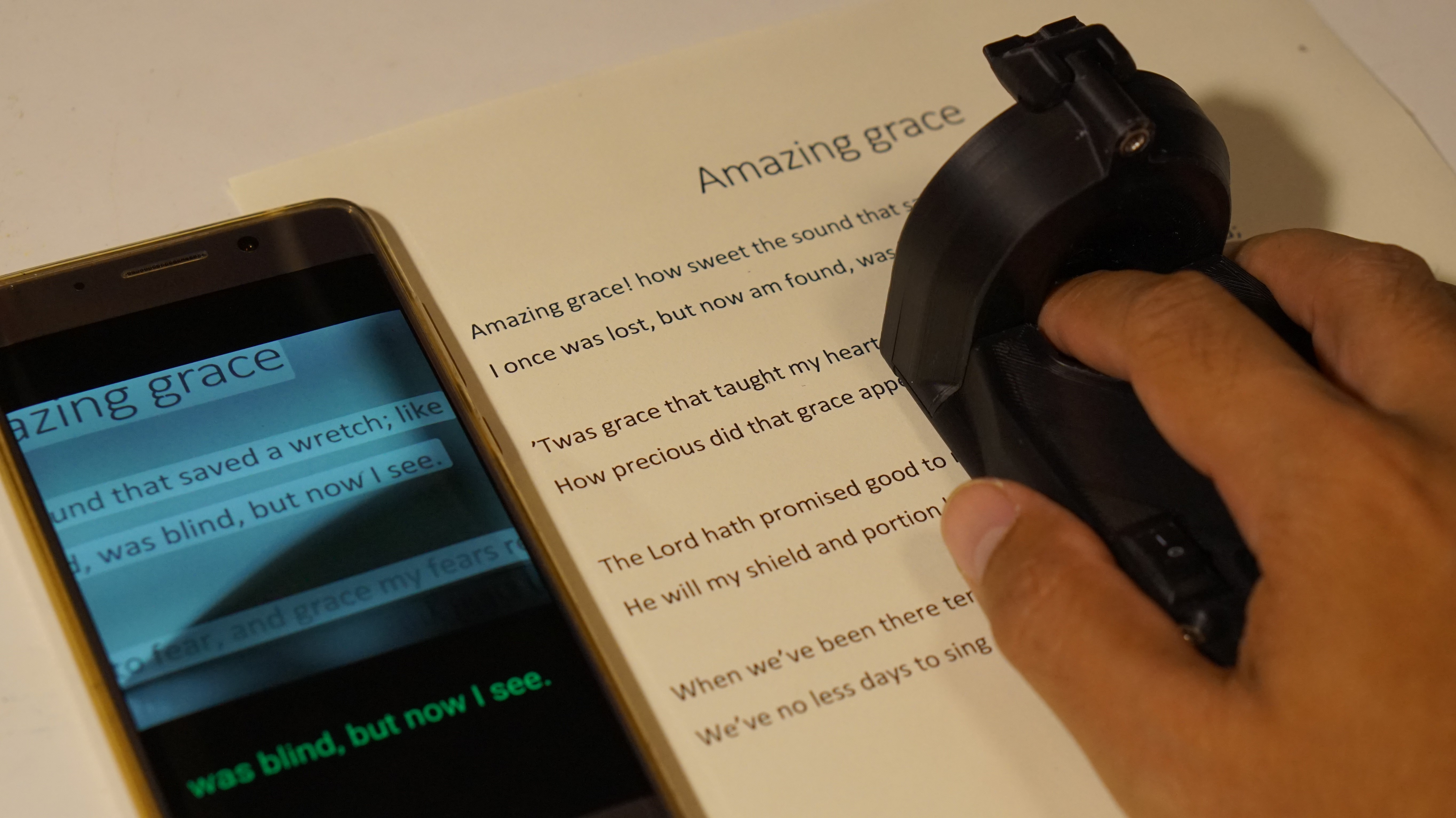 The ReadRing in action.  Its scanning the text of Amazing Grace on paper that's showing up on a smartphone that's triggering the rotary braille display in the ReadRing.
